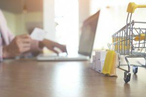 Imagem traz um carrinho de compras e uma pessoa usando um computador para ilustrar a defesa do consumidor